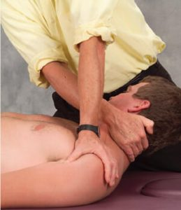 Figure 8: Extensor release. The therapist's left hand braces the anterior surface of the client's left shoulder, while the right hand reaches under the occipital ridge, hooks the fascia with soft finger pads, and right-rotates the client's head. The client inhales to a count of five while gently left-rotating head against the therapist's resistance. Upon exhalation the therapist produces a counterforce between his two hands by depressing the client's left shoulder while slowly sweeping along the occipital ridge to release tight capital extensors. .