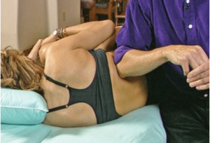 Fig. 4A: Client pulls knee to chest to inferiorly drag on the ilium as therapist's elbow lengthens QL and lumbodorsal fascia.