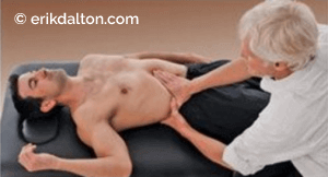 Image 4: To lift a kyphotic t-spine and activate an inhibited diaphragm, the client forcefully exhales as the therapist's webbed hands work all tissues binding the diaphragm. To enhance the release, the client performs slow pelvic tilts.