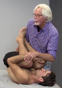 Image 4: To aid in disc imbibement, client pulls knees to chest and tucks chin. Therapist's left hand gently rocks the client so his right hand can come under the sacrum. Client is asked to perform slow pelvic tilts to hydrate discs.