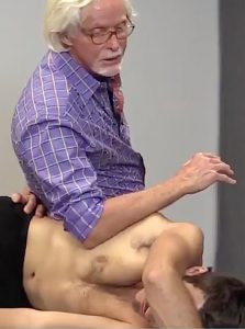 Image 5: Client grasps top of therapy table. Therapist's left hand snakes behind his back to secure client's right hip while his right forearm hooks the lateral fascia. Client is asked to pull down on therapy table against therapist's resistance to a count of five, then relax. To decompress discs and stimulate anti-gravity muscles, therapist's forearm lifts the thorax while his left hand resists. Repeat.