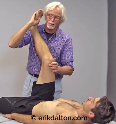 Image 1: With the client's hip flexed, the therapist slowly extends the knee to the first restrictive pain barrier. The client gently knee flexes against the therapist's resistance to a count of five and relaxes. Working with the client's nervous system, the therapist again extends the knee to the feather edge of the painful barrier and repeats the action until functional range of motion is restored.