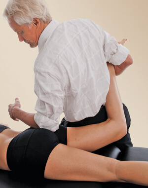 Figure 4. A counterforce occurs as the therapist's left forearm hooks the client's hip external rotators while her right leg is taken into internal rotation. Therapist assesses and releases hip hypertonicity.