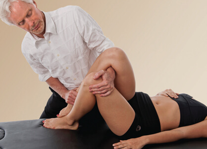 Figure 5. To posteriorly rotate client's right ilium, the therapist snakes his left arm under her right leg and grasps her left knee. Therapist left rotates client's hips and applies a counterforce between both hands to decompress the right fixated SI joint.