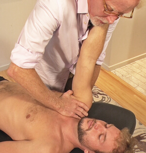 Image 5: the therapist's tight thenar eminence depresses the client's AC joint while protracting their shoulder.