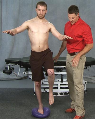 "Man demonstrating a one legged balance on ""wobble"" platform"