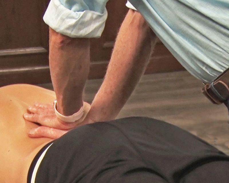 Image 2. Z-Joint Pain Provocation Test: Using soft palms, the therapist palpates the paravertebral tissues overlying the lumbar transverse processes and the client reports Z-joint tenderness.