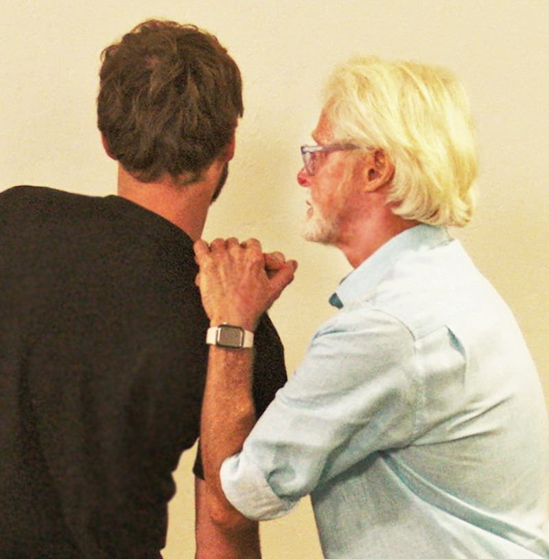 Image 4. Kemp's Test: The therapist asks the client to right rotate, right sidebend, and extend his torso. The therapist places both hands on the client's shoulder and gently depresses. Record as a positive if this maneuver reproduces or enhances the client's symptoms. However, if the pain follows a dermatomal pathway into the lower extremity, it may indicate sciatic nerve root compression.