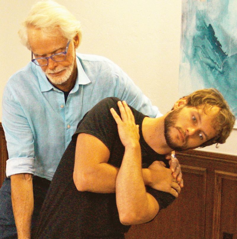 Image 5. Passive Sidebending Technique: With his right hand bracing the client's thigh, the therapist's left hand sidebends the client's lumbar spine to stretch the quadratus lumborum and decompress the Z-joints on the client's right side. The client is asked to gently right sidebend against the therapist's resistance to a count of five and relax, and the therapist again left sidebends the client to the next restrictive barrier. Repeat 3-5 times and retest using the Kemp's test.