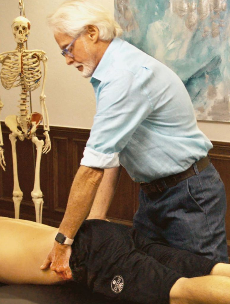 Image 6. Iliosacral Alignment Technique: The therapist's left hand lifts the client's left anteriorly/inferiorly rotated ilium and his right palm braces the right posterior superior iliac spine. The therapist gently pulls with his left hand while resisting with his right. The client is asked to gently push his left ilium toward the table to a count of five and relax. The therapist rotates the client's pelvis to the next restrictive barrier to restore Z-join alignment.